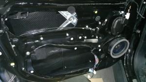 Proces montażu głośników i wygłuszenia drzwi wysokiej jakości matami bitumicznymi.